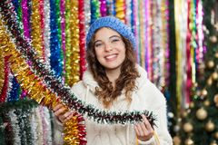 Young Woman Choosing Tinsels At Store Royalty Free Stock Photos