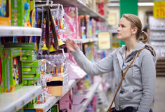 Young woman is choosing toys for her kid. Stock Photo