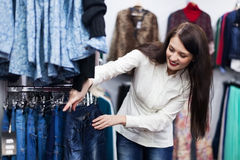 Young woman choosing trousers at boutique Stock Image