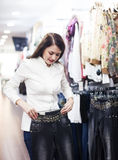 Young woman choosing trousers at market Royalty Free Stock Photo