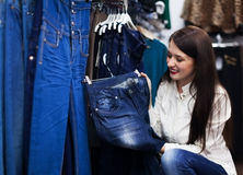 Young woman choosing trousers at shop Stock Image
