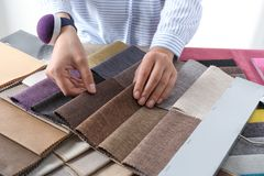 Young woman choosing among upholstery fabric samples, closeup. royalty free stock photography