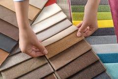 Young woman choosing among upholstery fabric samples, closeup royalty free stock photography