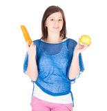 Young woman chose between apple and carrot over white background Stock Images