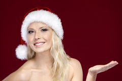 Young woman in Christmas cap gestures palm up Stock Photography