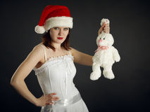 Young woman in Christmas cap holds a rabbit Royalty Free Stock Image