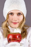 Young woman with Christmas decoration. Beautiful young woman in a white knitted cap holds in his hands Christmas decoration Royalty Free Stock Photos