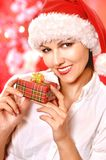 Young woman with Christmas gift. Cute young woman with Christmas gift on blurred background Stock Images