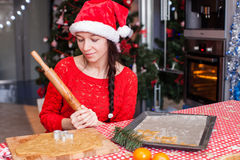 Young woman in Christmas hat baking gingerbread at Royalty Free Stock Images