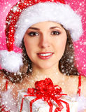 A young woman in a Christmas hat holding a present Royalty Free Stock Images