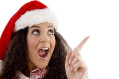 Young woman with christmas hat indicating upward Royalty Free Stock Photography