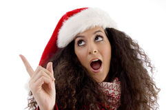Young woman with christmas hat pointing aside Stock Photography
