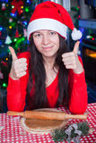 Young woman in Christmas hat raised thumbs up at Stock Photo
