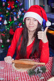 Young woman in Christmas hat raised thumbs up at Stock Photography