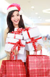 Young woman in christmas hat / santa with shopping bags and gift Royalty Free Stock Photos