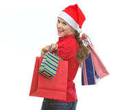Young woman in Christmas hat with shopping bags. Looking out Royalty Free Stock Image