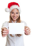 Young woman with christmas hat showing blank card Royalty Free Stock Photos