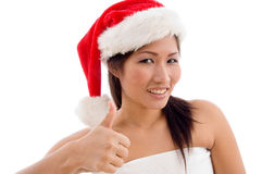 Young woman with christmas hat showing thumb up Stock Photos