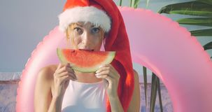 Young woman in Christmas hat in swimsuit, New Year theme stock video