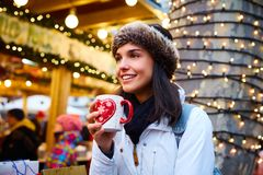 Young woman in christmas mood. Happy young woman drinking hot drink at christmas fair, smiling, looking away Royalty Free Stock Images