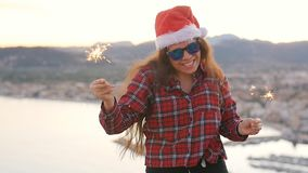 Young woman in christmas or new year coat and hat holding winter holiday sparkler and bengal fire outdoors. Young woman in christmas or new year coat and hat stock video footage