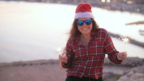 Young woman in christmas or new year coat and hat holding winter holiday sparkler and bengal fire outdoors. Young woman in christmas or new year coat and hat stock footage