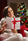 Young woman with christmas postcard in front of christmas tree Royalty Free Stock Images
