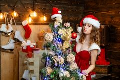 Young woman with christmas present boxes in front of christmas tree. Happy emotion. Euphoria. Crazy comical face. Smiling woman decorating Christmas tree at stock images