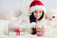 Young woman in christmas santa hat relaxing in bed Royalty Free Stock Photo