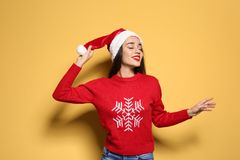 Young woman in Christmas sweater and hat. On color background stock photography