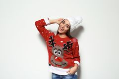Young woman in Christmas sweater and knitted hat. On white background stock photo