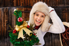 Young woman with Christmas tree in the front of rustic wood wall Royalty Free Stock Photography
