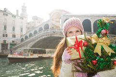 Young woman with Christmas tree and gift box in Venice, Italy Stock Image