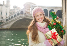 Young woman with Christmas tree and gift box in Venice, Italy Stock Images