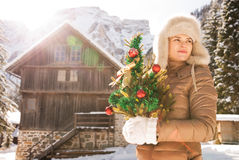 Young woman with Christmas tree standing near mountain house Stock Photos