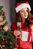Young woman by a christmastree. And champagner Stock Images