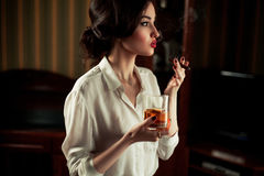 Young woman with cigar and glass of whiskey in retro atmosphere. Royalty Free Stock Photo