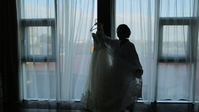 Young woman circles in dance keeping bridal dress in her right hand. stock video footage