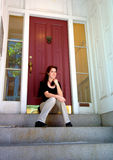 Young woman on city apartment steps. Young woman sitting on steps in front of red apartment door in a city royalty free stock photography