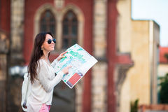Young woman with a city map in city. Travel tourist girl with map in Prague outdoors during holidays in Europe. Travel tourist woman with map in Prague outdoors royalty free stock photo