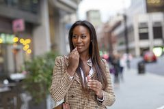 Young woman in the city putting on lipsgloss stock images