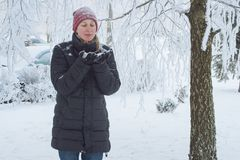 Young woman in the city in the snow. Heavy snowfall in the city and a young woman standing under the falling snow Stock Photos