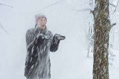 Young woman in the city in the snow. Heavy snowfall in the city and a young woman standing under the falling snow Royalty Free Stock Image