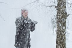 Young woman in the city in the snow. Heavy snowfall in the city and a young woman standing under the falling snow Royalty Free Stock Images