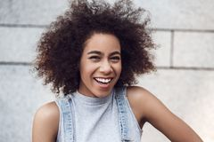 Young woman in the city street standing on gray wall looking camera laughing cheerful close-up stock photos