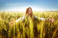 Young woman clasped her hands and ears. Of wheat Stock Images