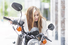 Young woman on the classic motorcycle in the street. Royalty Free Stock Photo