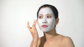 Young woman clay face mask peeling natural with purifying mask on her face stock footage