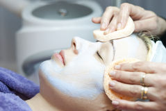 Young woman with clay facial mask. Beautiful young woman lies on a table in a beauty spa getting a treatment stock photos