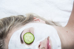Young woman with clay facial mask in spa salon Stock Photos